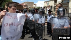 "Armenia - A protester outside the presidential palace in Yerevan holds a poster demanding ""punishment"" for businessman Ruben Hayrapetitian and his bodyguards, 1Jul2012."