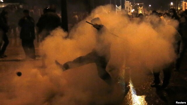 A protester kicks away a gas canister during clashes with riot police during a 48-hour strike by the two major Greek unions in central Athens on November 7.