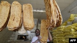 "An Iranian baker shows a traditional bread, known locally as ""Barbari"", during the Muslim holy month of Ramadan, in Tehran, June 22, 2016. File photo"