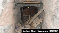 Металлическая дверь в двухэтажном траверсе завалена мусором
