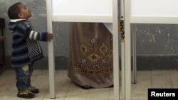 Ребенок смотрит, как его мать голосует на выборах в Египте в 2012 году