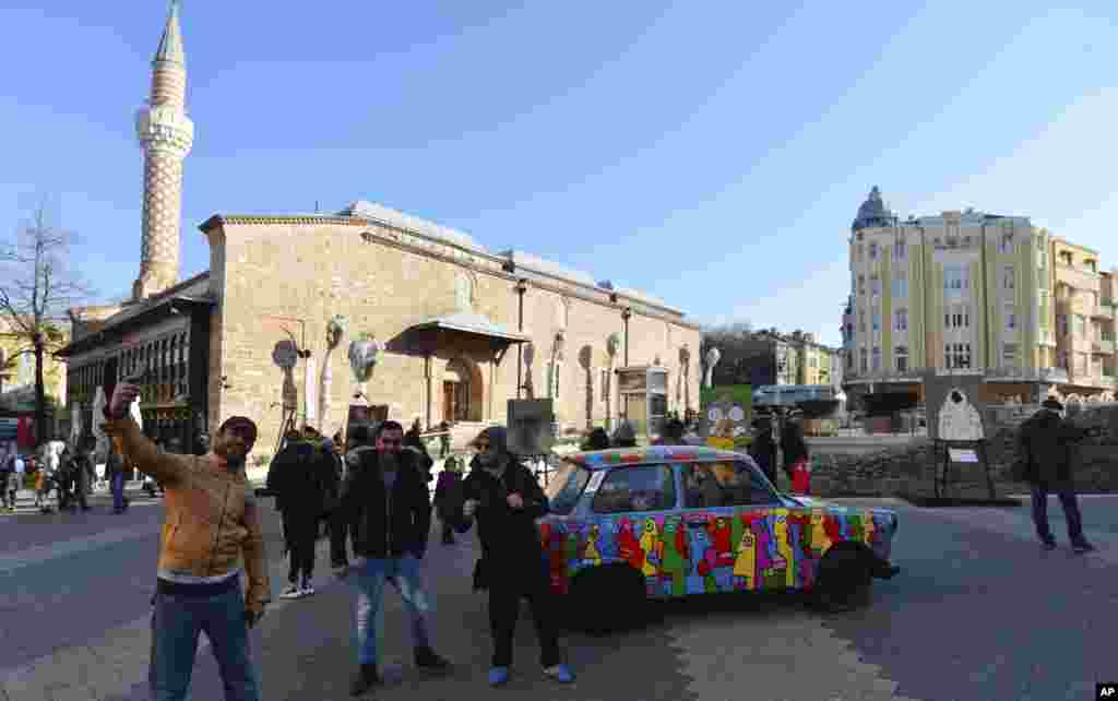 People take selfies in Plovdiv with a painted Trabant. The East German car is on display as part of Art Liberty, a traveling exhibition marking the 30th anniversary of the fall of the Berlin Wall.