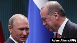 Turkish President Recep Tayyip Erdogan (right) and Russian President Vladimir Putin shake hands after a joint press conference following a meeting in Ankara on September 28.