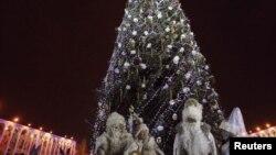 Жители Бишкека в костюмах Санты Клауса, Деда Мороза и Снегурочек у Новогодней ёлки.