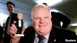 Роб Форд демонстрирует журналистам пластиковую куколку - фигурку игрушечного мэра Торонто