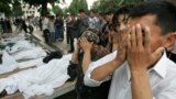 People pray near the bodies of victims of a massacre in the Uzbek city of Andijon in 2005 that left hundreds dead.