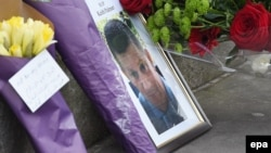 A makeshift memorial to the victims of the terror attack includes a photograph of British policeman Keith Palmer, who was stabbed to death by the assailant.