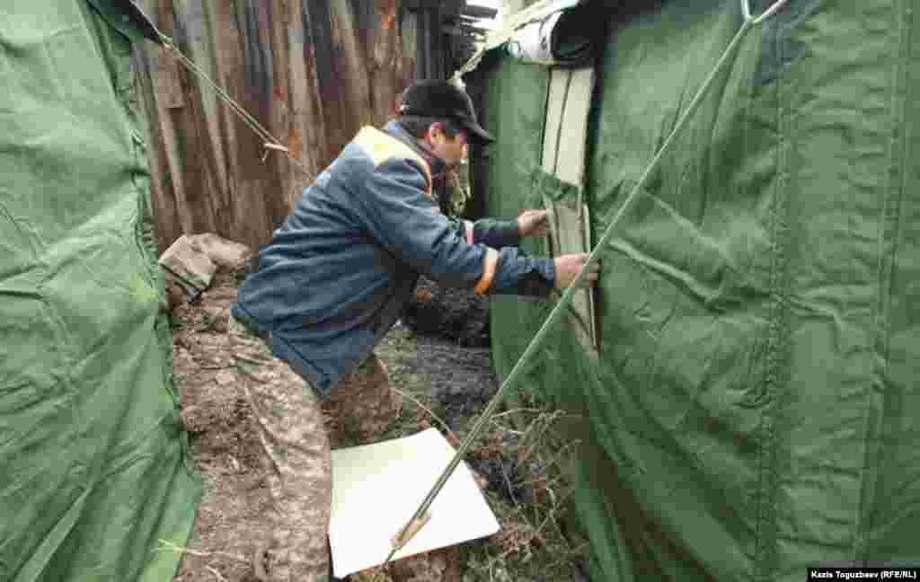 Сотрудник службы спасения устанавливает окошко в палатке.