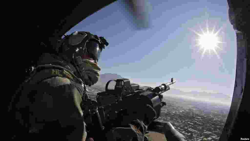 A French gunner remains alert and ready aboard a helicopter during a flight above Kapisa Valley, Afghanistan.