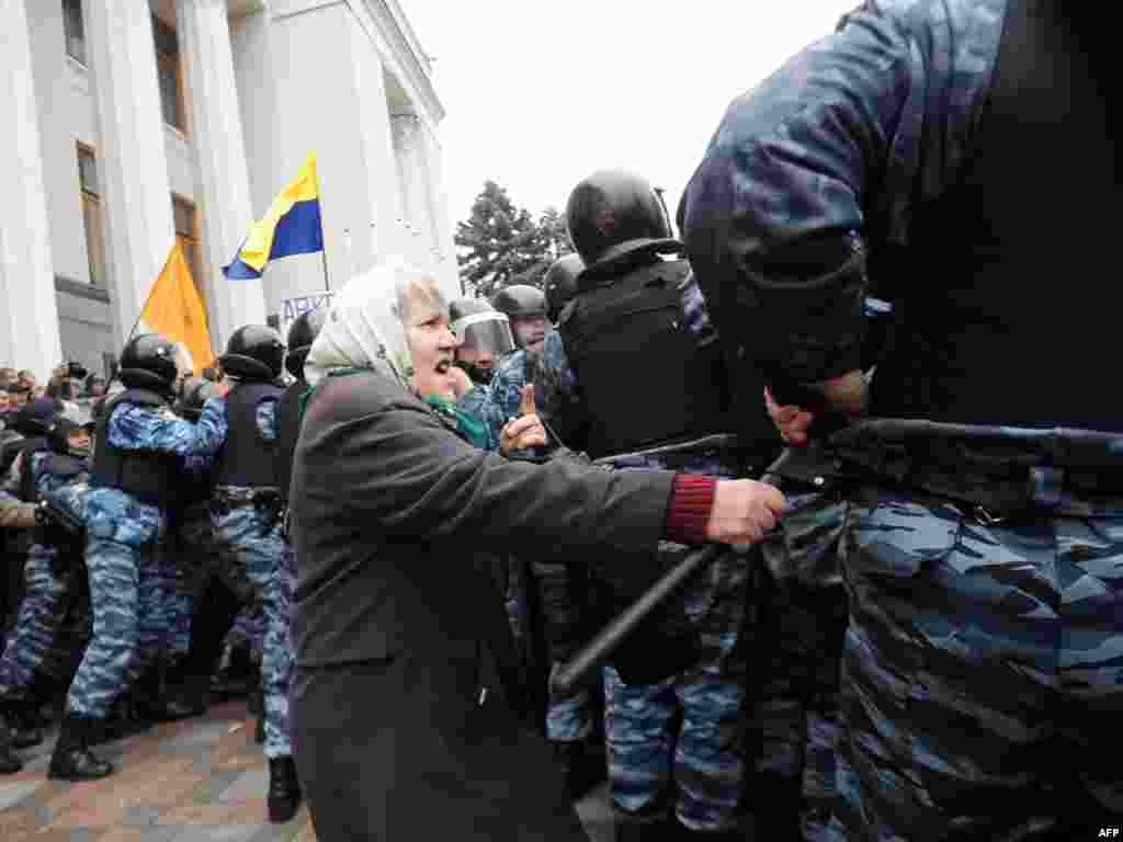 An elderly woman fights with a police officer during a protest in front of the parliament in Kyiv, Ukraine. (Sergey Polezhaka for AFP)
