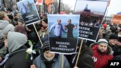 Сторонники оппозиции, протестующие против итогов выборов в Госдуму, держат в руках транспаранты с изображением Владимира Путина и Дмитрия Медведева. Москва, 10 декабря 2011 года.