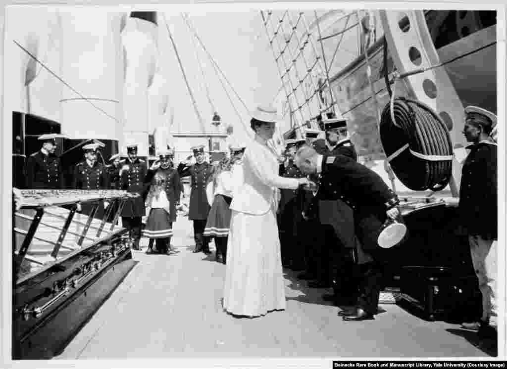 Empress Aleksandra being greeted aboard the Standart, the imperial yacht that served the tsar's family for holidays and official tours. In the background, her young daughters, known as Russia's grand duchesses, are saluted by the crew.