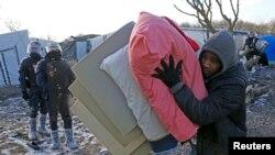 Мигрант несет постельные принадлежности в лагере в городе Кале. 7 марта 2016 года.
