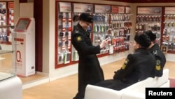 A Russian cadet uses a mobile phone to photograph other cadets in a phone shop in St. Petersburg.