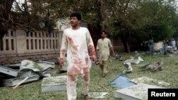 Njerëzit ecin në vendin e sulmit vetëvrasës në Xhalalabad të Afganistanit që për cak e kishte Konsullatën e Indisë