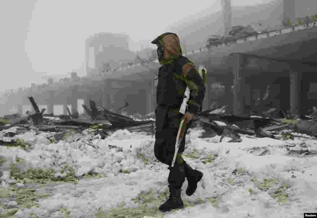 """A member of the self-proclaimed """"Donetsk People's Republic"""" forces walks near a building, destroyed during battles with the Ukrainian armed forces, at Donetsk airport. (Reuters/Aleksandr Ermochenko)"""