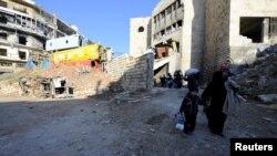 Алеппоның шығысындағы аудандардың бірінен кетіп бара жатқан тұрғындар. Сирия, 9 желтоқсан 2016 жыл.