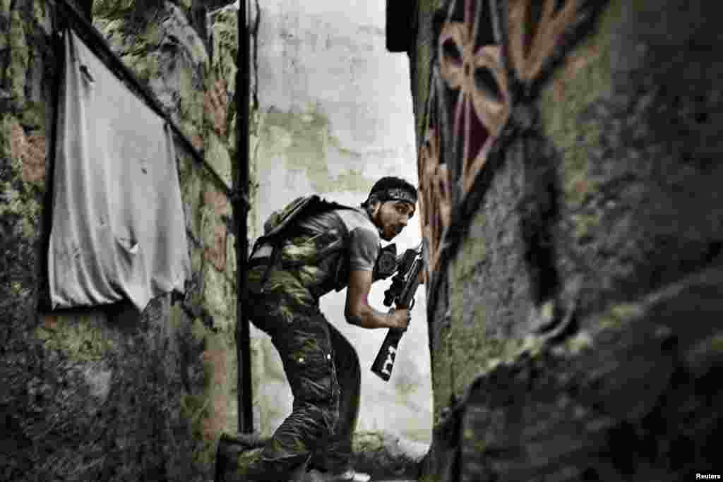 """Fabio Bucciarelli of Italy, a photographer working for the Agence France-Presse, won second prize in the Spot News Stories category with the series """"Battle to Death."""" The picture shows a Free Syrian Army fighter taking up a position during clashes with government forces in the Sulemain Halabi district in Aleppo."""