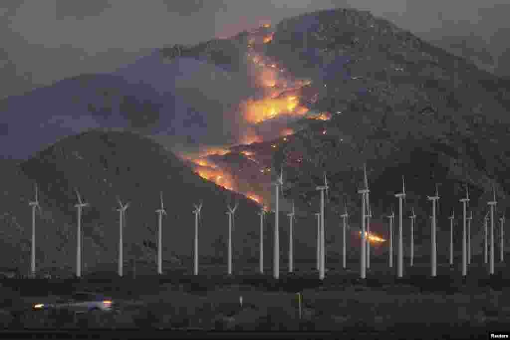 Wind turbines against a backdrop of wildfires, fanned by high winds, spreading up the slopes of the San Jacinto Mountains in southern California. (Reuters/David McNew)