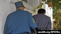 Ўзбек милиционери ҳибс қилинган шахсни олиб кетмоқда.