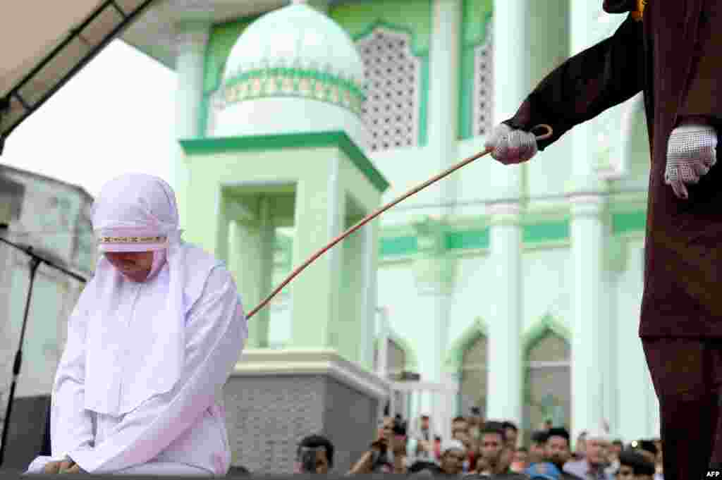 A 20-year old Muslim woman gets caned after being caught in close proximity to her boyfriend in Banda Aceh, Indonesia. Aceh is the only province in the predominantly Muslim country that applies Shari'a law. Public canings for breaches of Islamic code happen on a regular basis and often attract huge crowds. (AFP/Chaideer Mahyuddin)