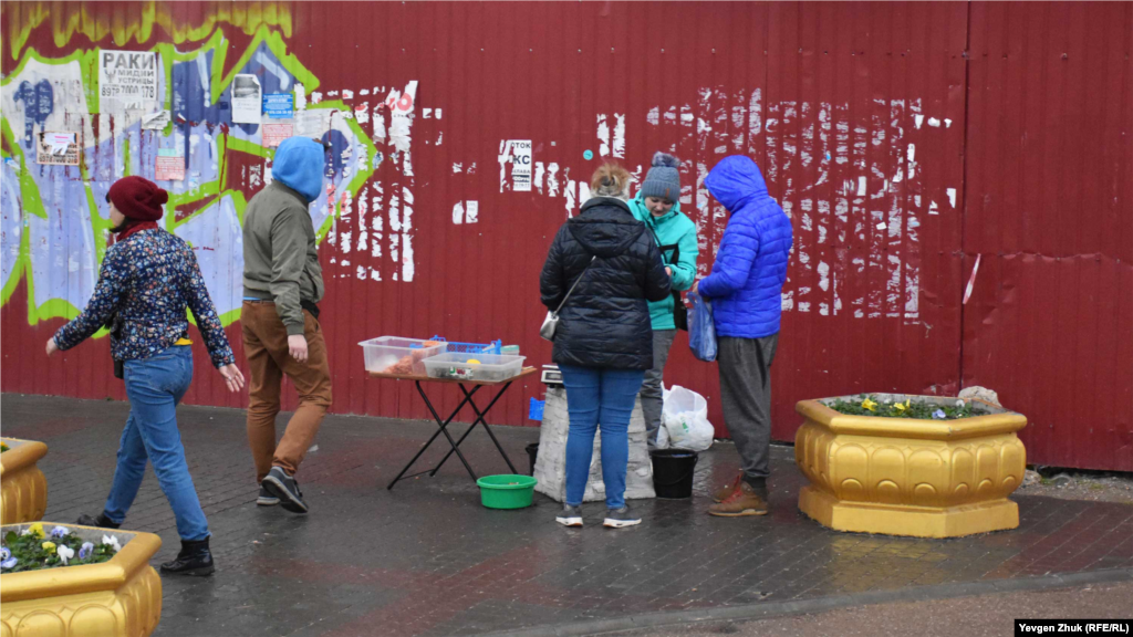 Біля руїн кінотеатру «Родіна» дівчина продає креветки та мідії