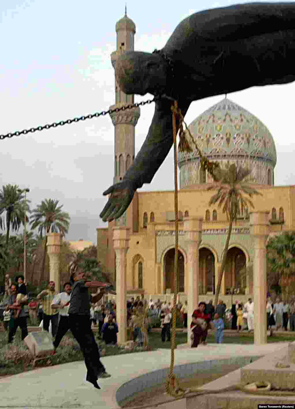 "An Iraqi man throws stones at a statue of Saddam Hussein on April 9, 2003. The day before this photograph was taken a U.S. plane had attacked the Al-Jazeera offices in Baghdad, killing Tomasevic's colleague and friend Tareq Ayoub. Recalling the day he took the iconic images of the statue being toppled, Tomasevic said: ""I didn't care, I just wanted to finish the job and go home."""