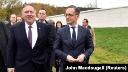 U.S. Secretary of State Mike Pompeo (left) and German Foreign Minister Heiko Maas walk along remains of the wall at a memorial site during their visit to the village of Moedlareuth near Hof, Germany, on November 7.