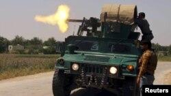 Құндыз уәлаятында Талибан содырларына көлік үстінен оқ атып тұрған полиция өкілі. Ауғанстан, 3 мамыр 2015 жыл.