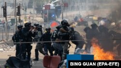 Politehnika uniwersitetiniň daşynda bolan çaknyşyklarda Hong Konguň polisiýasy demokratiýa tarapdar protestçileri tussag edýär. 18-nji noýabr, 2019 ý.