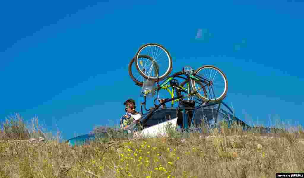 На дамбе озера мужчина закрепляет велосипеды на крыше автомобиля