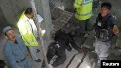 Ауғанстан полициясы Кабулда қаза тапқан жанкештінің денесін тексеріп жатыр. Ауғанстан, 16 сәуір 2012 жыл.