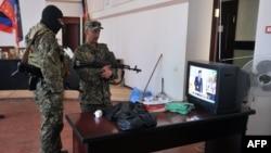 Вооруженные пророссийские активисты смотрят новости по ТВ в захваченном здании горсовета Краматорска