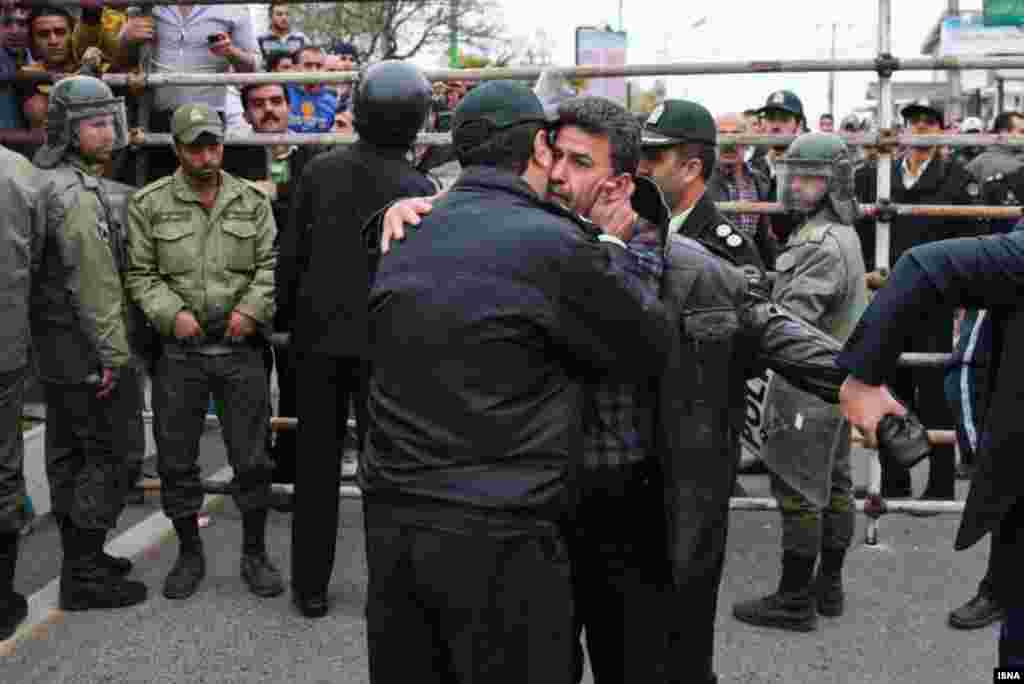 A member of the security forces thanks the victim's father, Abdolghani Hosseinzadeh, for the family's decision to forgive the killer.