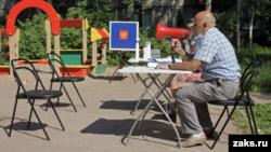 В Пушкине устроили голосование на лавочке во дворе дома. Мобильный УИК перемещается вдоль дома в течение дня. Людей зазывают проголосовать через мегафон