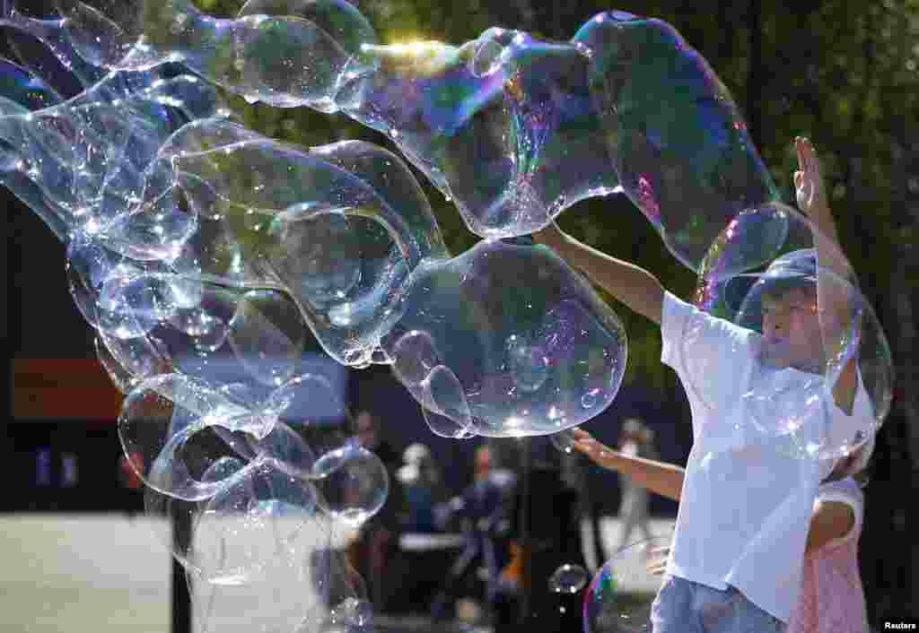 Children play with soap bubbles made by a busker on the South Bank in London. (Reuters/Andrew Winning)
