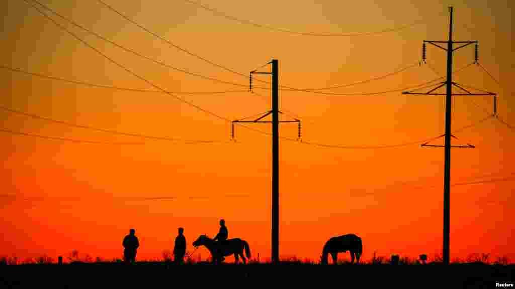 Местные жители с лошадьми под линией электропередачи. Город Арал.