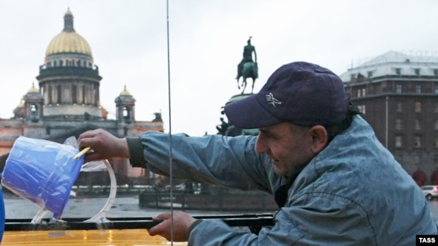 "Russia -- A protester taps a fake ""blue light"", a blue bucket turned upside-down, to a roof of his car in St. Petersburg, 22Apr2010"