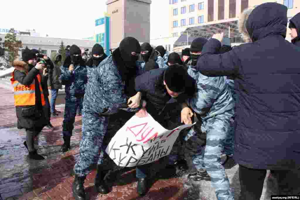 Спецназ забирает человека, в руках которого плакат с надписью: «Дулат — жертва системы».