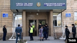 Police stand at the entrance to the Almaty Fashion Design College following the blast.