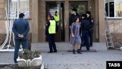 Сотрудники полиции и человек в гражданском у здания колледжа. Иллюстративное фото.