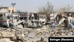 Damaged vehicles are seen at the site of a car bombing in Qalat, capital of Zabul Province, on September 19.