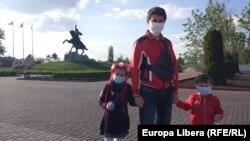 Un tată cu doi copii, cu măști medicinale, în fața monumentului lui Suvorov din centrul Tiraspolului, veniți pentru a marca Ziua Victoriei. 9 mai 2020
