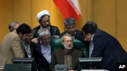 Iranian parliament speaker Ali Larijani, seated at center, talks with a group of lawmakers in a session of parliament to debate proposed cabinet by President Hassan Rouhani, in Tehran, Iran, Thursday, Aug. 17, 2017. (AP Photo/Vahid Salemi)