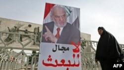 سيدة عراقية تمر أمام ملصق إنتخابي في بغداد شباط 2010.