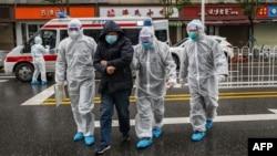 Арнаулы киім киген дәрігерлер науқас адамды ауруханаға әкеле жатыр. Ухань, Қытай, 26 қаңтар 2020 жыл.