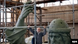 Russian artist Salavat Scherbakov climbs the scaffolding around his model for a monument of St. Vladimir at a workshop in Moscow on May 28, 2015.