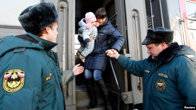 Russian Emergencies Ministry workers help a woman with a child out of a train as refugees from eastern Ukraine arrive at a railway station in the southern city of Stavropol on February 24.