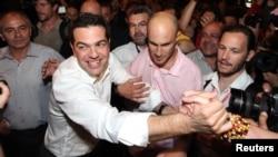 Лидер греческого леворадикального движения СИРИЗА Алекс Ципрас (слева) празднует успех на парламентских выборах. 6 мая 2012 г