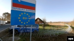 A Slovenian police van is in attendance at a barbed-wire barrier behind a Republic of Slovenia and European Union sign in the village of Rigonce, on Slovenia's border with Croatia on November 12.